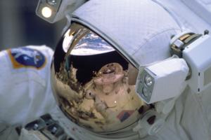 Spejling af jorden i astronauts hjelm med skærm belagt af guld